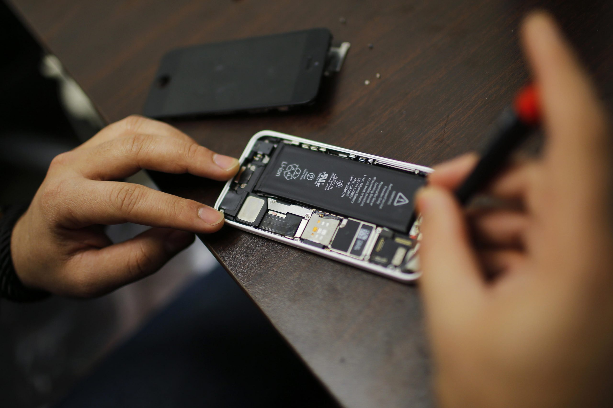 A worker tries to repair an iPhone in a repair store in New York